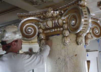 A CSS artisan works on an ornate gilded and glazed capital