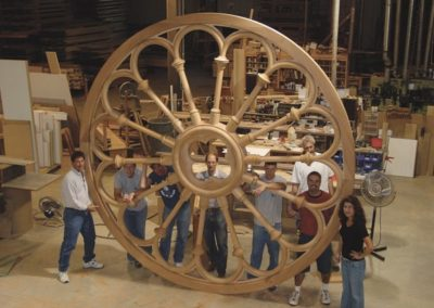The newly replicated mahogany frame is proudly displayed by the artisans who created it.
