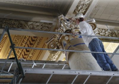 A CSS artisan works on a gilded and glazed capital
