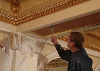 A CSS artisan applies finishing touches to a ceiling section