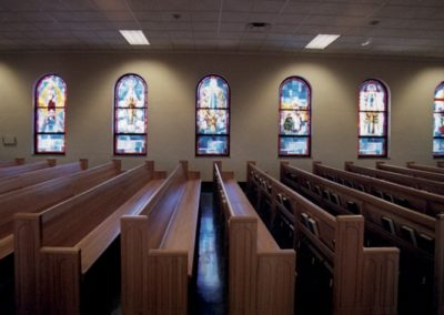 New stained glass fills the once clear wall of the church
