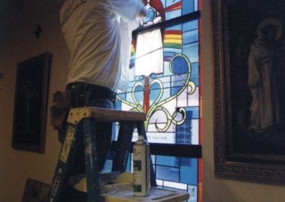 A new stained glass window is installed by a CSS artisan