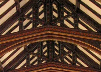 Decorative painting with stenciled designs subtly grace the wooden beams