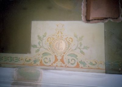 A cleaned section of the ceiling reveals the beautiful decorative painting