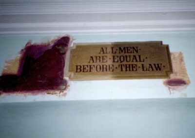 The removed paint around the plaque in the courtroom reveals painted over decorative elements that have now been restored