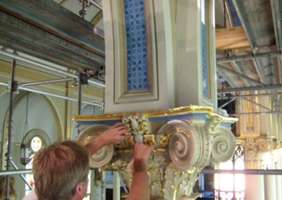 A CSS artisan applies gold leaf to a painted capital