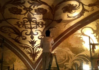 A CSS artisan gilds the Sanctuary ceiling