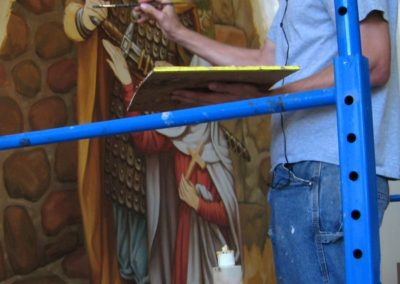 A CSS artist creates the new Sanctuary mural for St. Genevieve