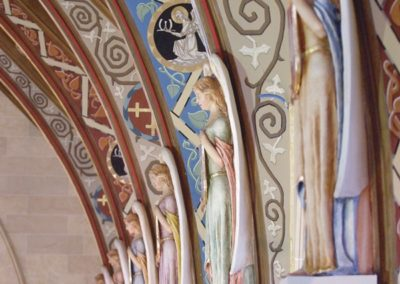 Polychrome painted life-size angel figures that stand at the base of the ceiling beams