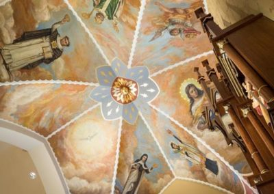 Above the sanctuary, the apse ceiling is adorned with six murals depicting Mary surrounded by saints
