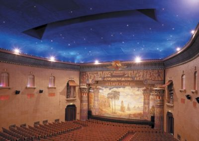 "The restored main house with elaborate proscenium arch, painted curtain, and ""starry"" domed ceiling"
