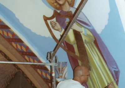 A CSS artist works on restoring an angel on the ceiling