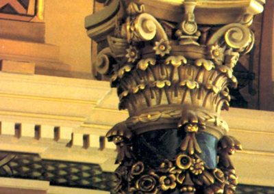A faux marble pillar and highly ornate capital with gilded dimentional floral weaths