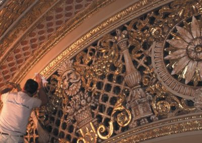 An artisan from Conrad Schmitt Studios puts the finishing touches on a gilded arch
