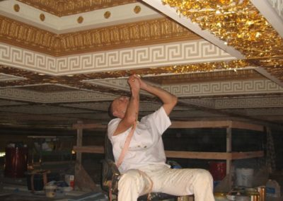 A CSS artisan applies gold leaf to a coffer